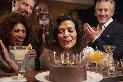 Group Of Middle Aged Friends Celebrating Birthday In Bar royalty free stock image