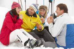 Group Of Middle Aged Friends Eating Sandwich. On Ski Holiday In Mountains stock photography