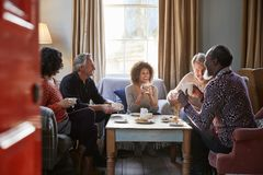 Group Of Middle Aged Friends Meeting Around Table In Coffee Shop royalty free stock photography
