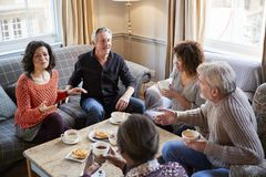 Group Of Middle Aged Friends Meeting Around Table In Coffee Shop royalty free stock photo