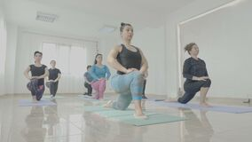 Group of middle aged women toning their bodies during a yoga class session in a fitness studio -. Group of middle aged women toning their bodies during a yoga stock footage