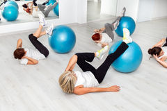 Group of middle aged women working out with fitness balls. Group of middle aged women working out with fitness balls in health center stock photography