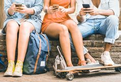 Group of millennial friends having fun spending time together with mobile smartphones and skateboard - Youth friendship concept royalty free stock photography