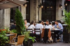 Group of millennials eating dinner outside at upscale restaurant royalty free stock photo