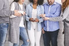Group of millennials reaching hands to cellphone stock photography