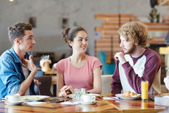 Friends in cafe. Group of millennials talking by lunch in new cafe or diner royalty free stock images