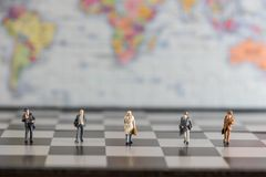 Group of miniature businessmen walking in the chess board royalty free stock image