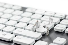 Group of miniature criminalists inspecting computer keyboard.  Cybercrime concept. Macro photo Stock Photography