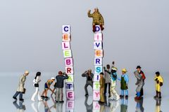 Group of Miniature diverse figurines people walking around a Group Of Letters forming Words Spelling. `Celebrate Diversity on grey background stock images