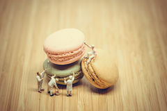 Group of miniature painters coloring macaroon. Color tone tuned. Royalty Free Stock Photo