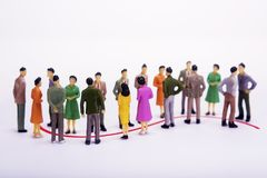 Group of miniature people over white background. Group of miniature people over white background standing in line Stock Images