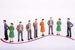 Group of miniature people over white background standing in line.  Stock Images