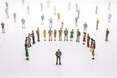 Group of miniature people over white background standing in line. Or circle royalty free stock photography