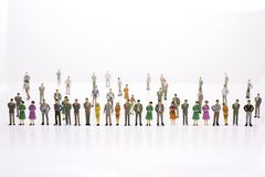 Group of miniature people over white background standing in line stock photos