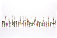 Group of miniature people over white background standing in line stock image