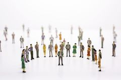 Group of miniature people over white background standing in line Royalty Free Stock Photography