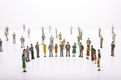 Group of miniature people over white background standing in line stock images
