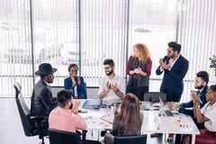 Group of mixed-race diverse co-workers discussing new project in office. Red-haired women boss and her Indian male assistant applaud to african men wearing hat royalty free stock image