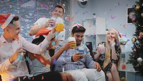 Group of mixed race friends celebrating Christmas in confetti blowing. While making cheers and blowing party whistles at home stock video