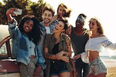 Selfie on road trip. Group of mixed race friends taking a selfie near the car. Young men and women together on road trip making selfie stock images