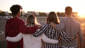 Group of mixed race friends walking embracing and having fun together in city. They are two girls and two boys in their stock video footage