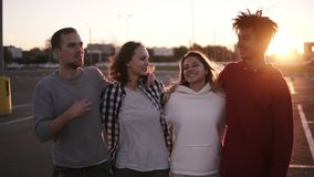 Group of mixed race friends walking embracing and talking together in city. They are two girls and two boys in their stock video footage