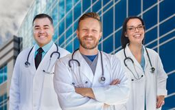 Group Of Mixed Race Male and Female Doctors or Nurses by Hospital. Group Of Mixed Race Male and Female Doctors or Nurses In Front of Hospital Building royalty free stock images