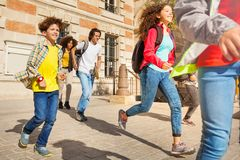 Group of mixed race teens running after classes. Group of mixed race teenage boys and girls, running after the classes in the end of a day Royalty Free Stock Photography
