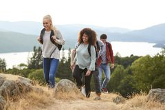 A group of mixed race young adult friends smiling while hiking to a mountain summit royalty free stock images