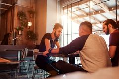 Group of mixed race young men talking in lounge bar. Multiracial friends having good time communicating in cafe. And drinking coffee Stock Photo