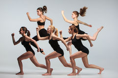 The group of modern ballet dancers. Dancing on gray background Stock Photography