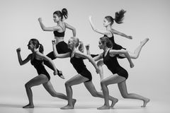 The group of modern ballet dancers. Dancing on gray background. The black and white or colorless photo Royalty Free Stock Images