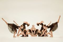 The group of modern ballet dancers. Dancing on gray studio background Royalty Free Stock Photo