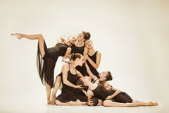 The group of modern ballet dancers. Dancing on gray studio background Royalty Free Stock Image