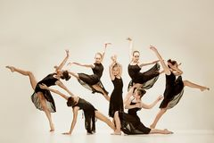 The group of modern ballet dancers. Dancing on gray studio background Stock Photos