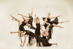 The group of modern ballet dancers. Dancing on gray studio background Stock Photo
