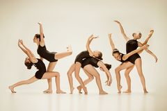 The group of modern ballet dancers. Dancing on gray studio background Royalty Free Stock Images