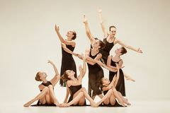 The group of modern ballet dancers. Dancing on gray studio background Royalty Free Stock Photos