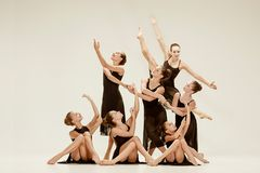 The group of modern ballet dancers. Dancing on gray studio background Stock Photography