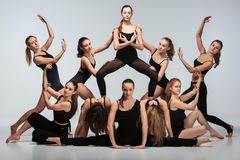 The group of modern ballet dancers. Posing on gray background Stock Photography