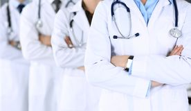 Group of modern doctors standing as a team with arms crossed in hospital office. Physicians ready to examine and help patients.