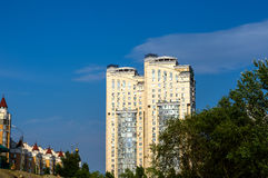 Group of modern multi-storey yellow and white big houses on background of blue sky Royalty Free Stock Images