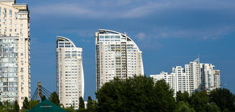 Group of modern multi-storey yellow and white big houses on background of blue sky Stock Images