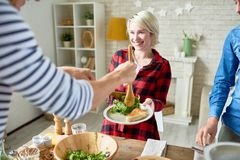 Happy Friends Having Dinner Together. Group of modern young people standing at big table with food on it preparing dinner together, focus on happy blonde women Royalty Free Stock Photography