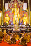Group of monks in sitting in front of Buddha standing images ins Royalty Free Stock Photos