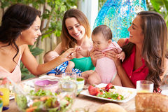 Group Of Mothers With Babies Enjoying Outdoor Meal At Home Stock Image
