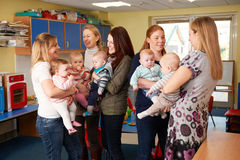 Group Of Mothers With Babies Meeting At Playgroup. Mothers Meeting At Baby Group Royalty Free Stock Photography