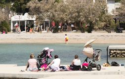 Group of mothers with baby strollers sitting on the beach in spring off-season. Vodice, Croatia - May 2, 2019: Group of mothers sitting on the beach in spring royalty free stock photo