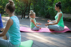 Group of mothers and daughters doing exercise practicing yoga ou Stock Photo