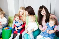 Group of mothers with kids. Group of mothers with their kids gathered to talk, toddlers have a launch Stock Image